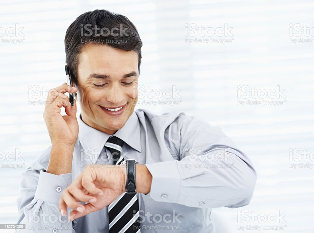 Successful business man checking time and using phone royalty-free stock photo