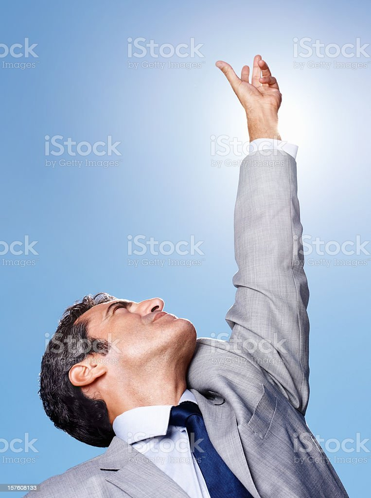 Portrait of a successful middle aged business man pointing up at blue...