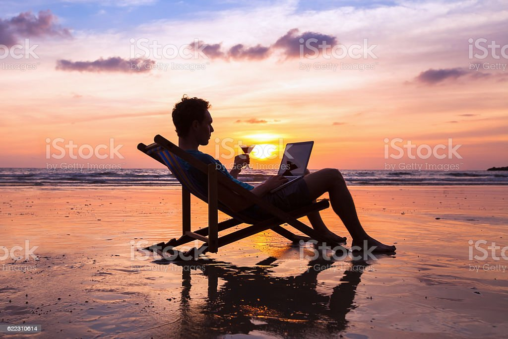 successful business man reading emails on laptop on the beach stock photo