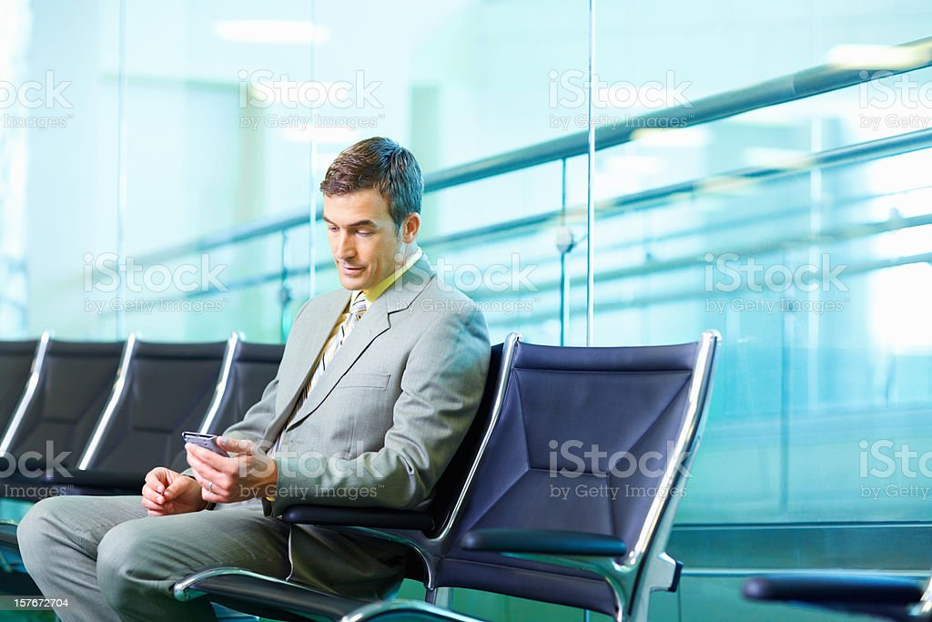 Successful business man reading text message at airport royalty-free stock photo