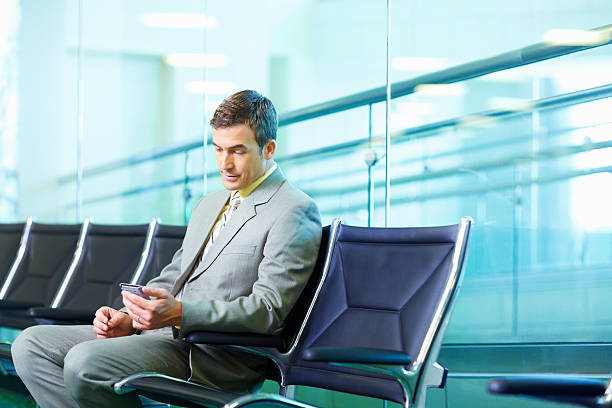 Successful business man reading text message at airport stock photo