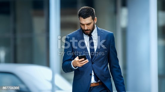 istock Successful Business Man Uses Smartphone While Walking on the Big City Business District Street. 867704366