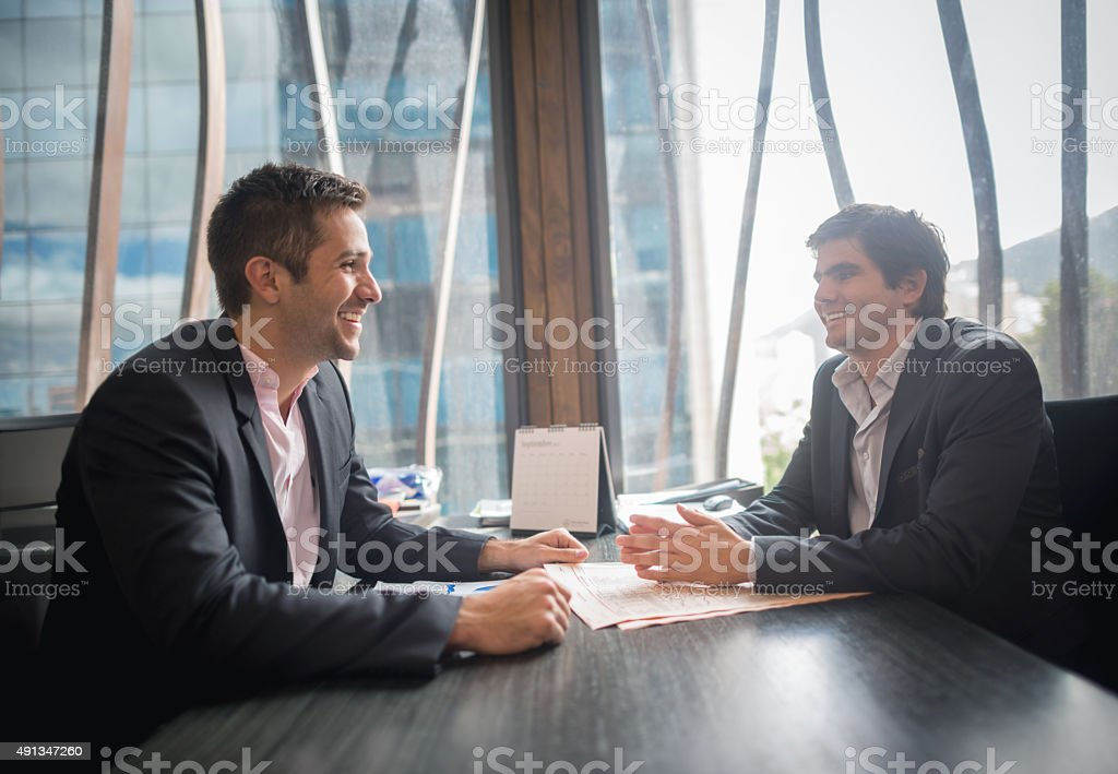 Successful business men in a meeting looking happy stock photo