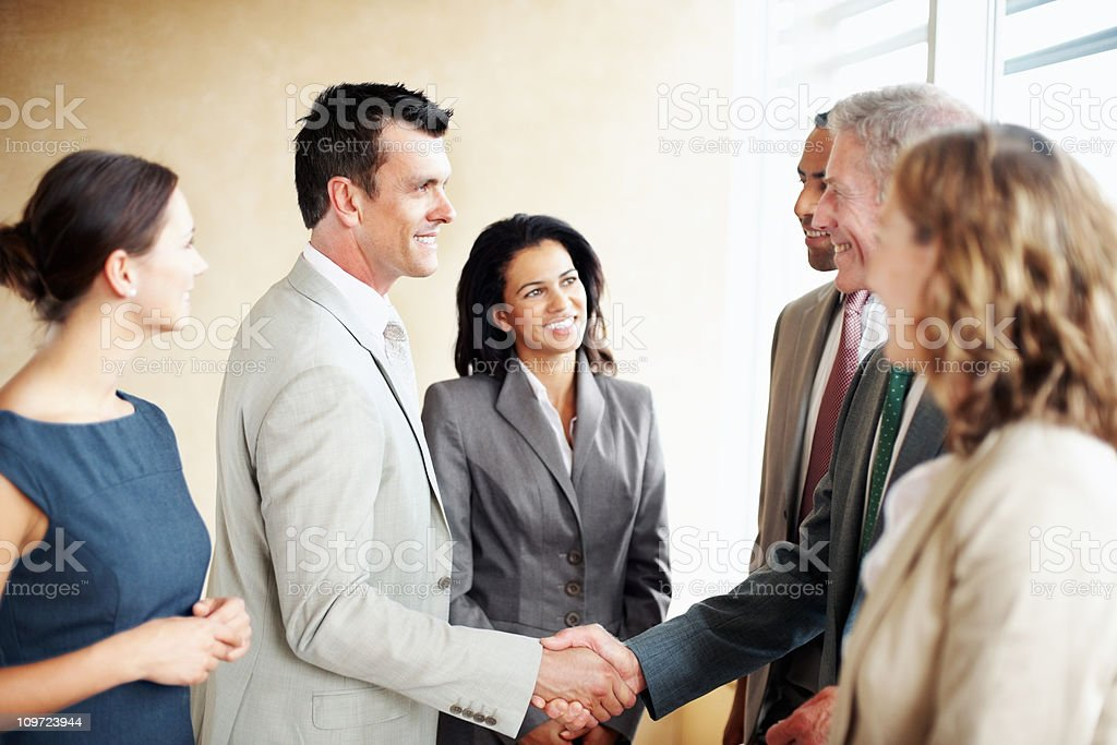 Successful business men shaking hands and team royalty-free stock photo