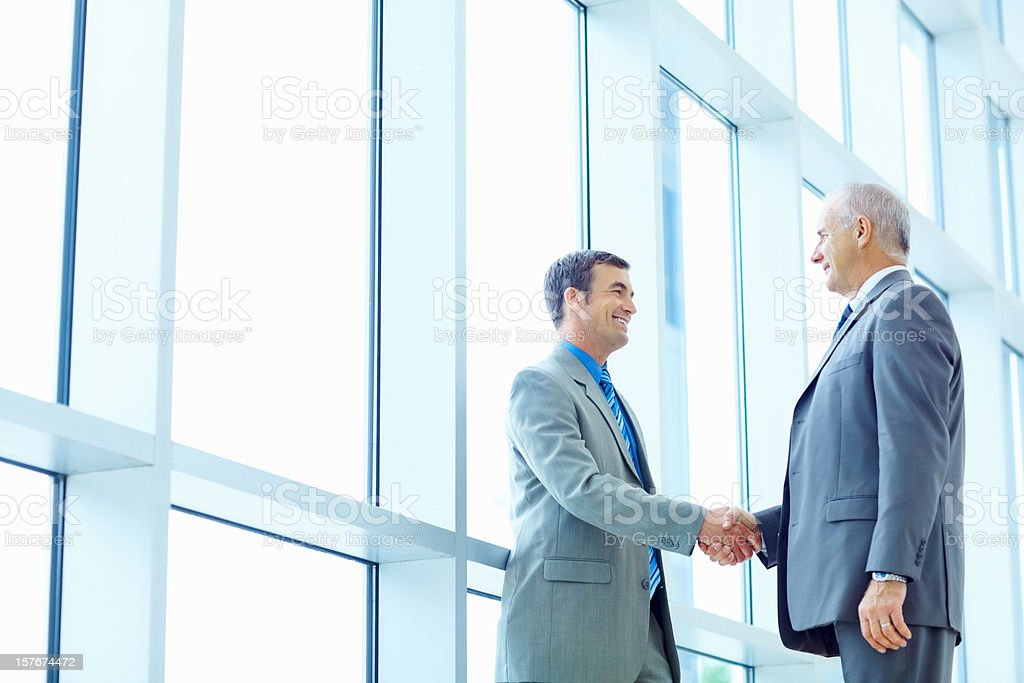 Successful business men shaking hands at office stock photo