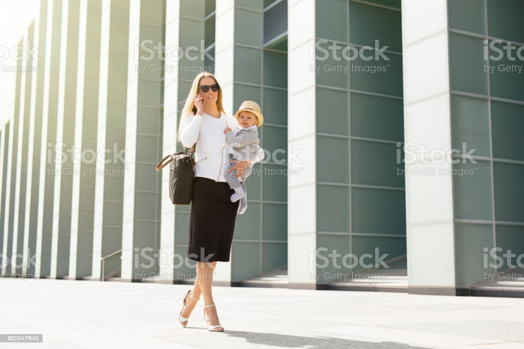 Mère d'entreprise prospère dans la ville avec le bébé dans ses mains - Photo