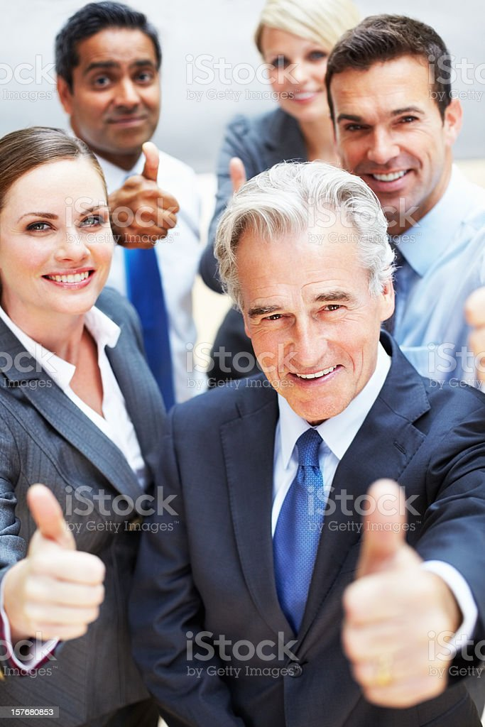 Successful business people giving you a thumbs up sign royalty-free stock photo