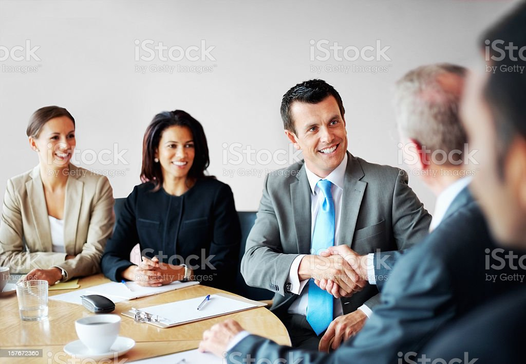 Successful business people shaking hands in a conference room royalty-free stock photo