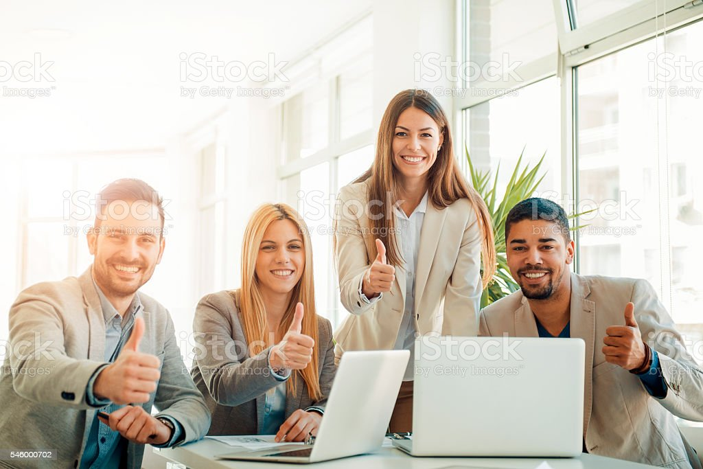 Successful business people with thumbs up stock photo