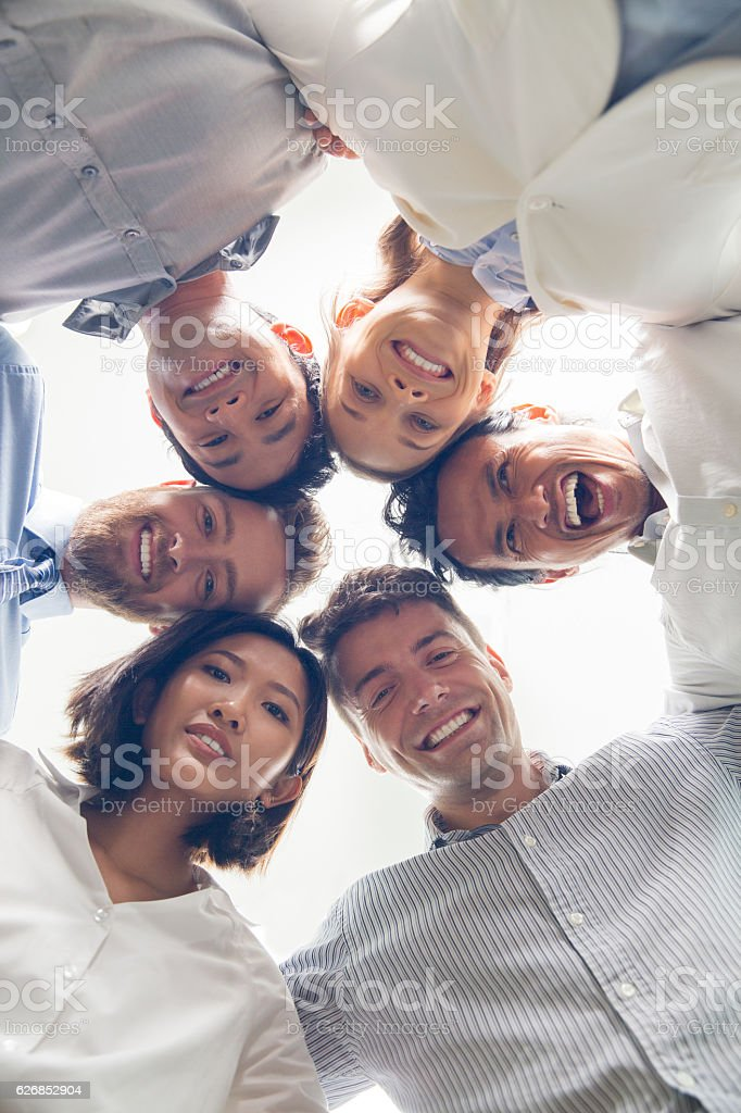 Successful business team embracing and smiling stock photo