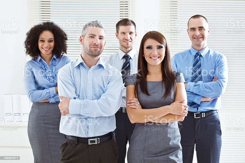 Successful Business Team Portrait of five business people standing in two rows in an office and smiling at camera. 25-29 Years Stock Photo