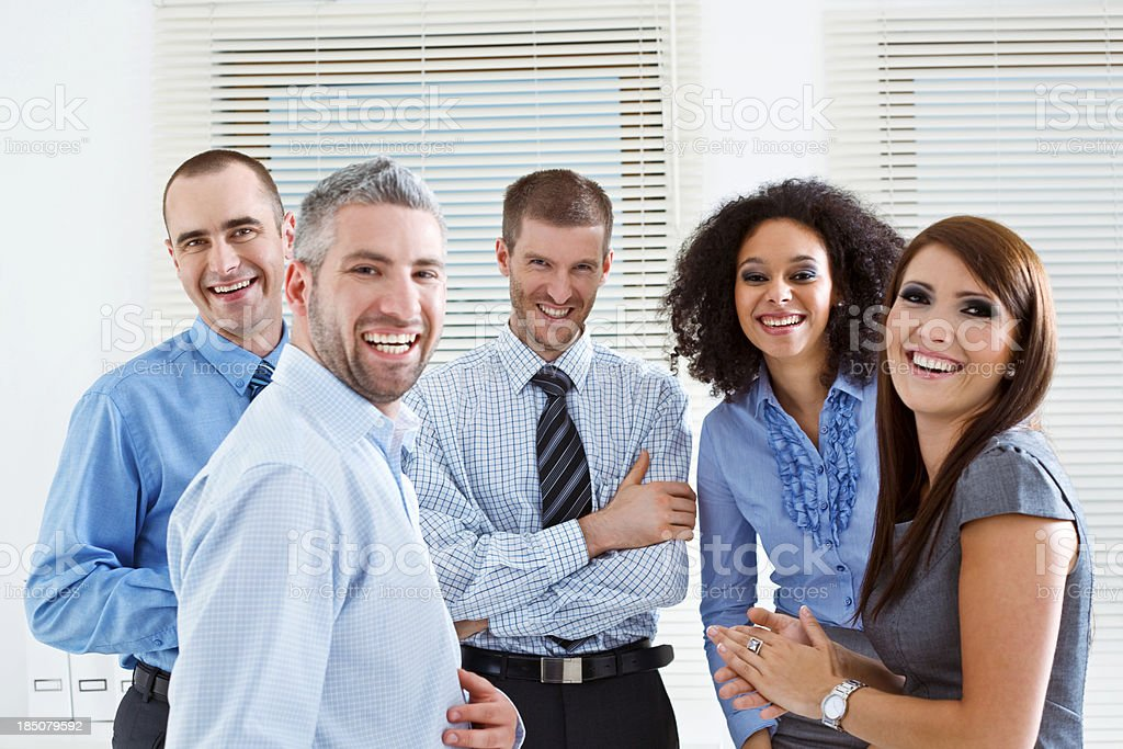Successful Business Team Five happy business people standing in an office and laughing at camera. 25-29 Years Stock Photo