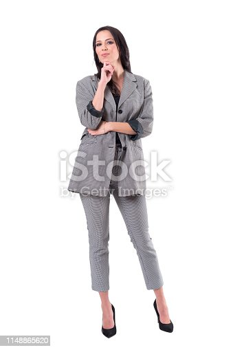 Successful business woman in suit looking at camera with hand under chin. Full body isolated on white background.