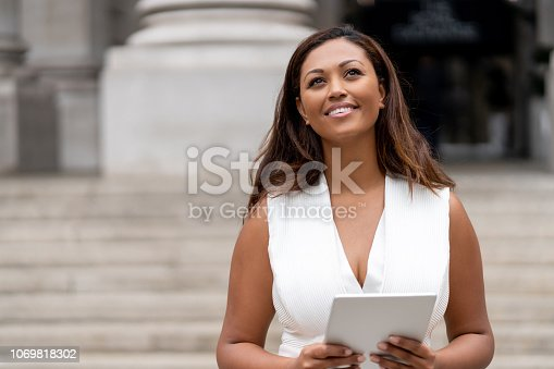 istock Successful business woman using a tablet computer outdoors 1069818302