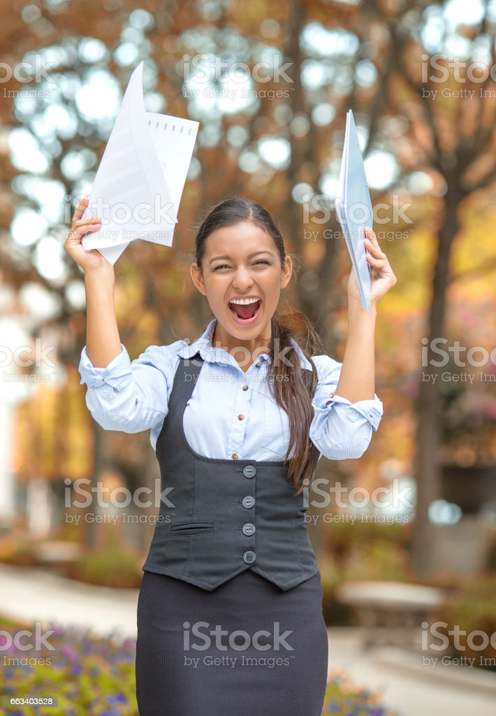 Successful business woman with arms up celebrating stock photo
