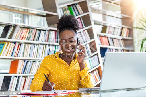 1053499704 istock photo Successful business woman working at the office, African American woman talking on her mobile phone and working on laptop. Small business entrepreneur concept 1176794224