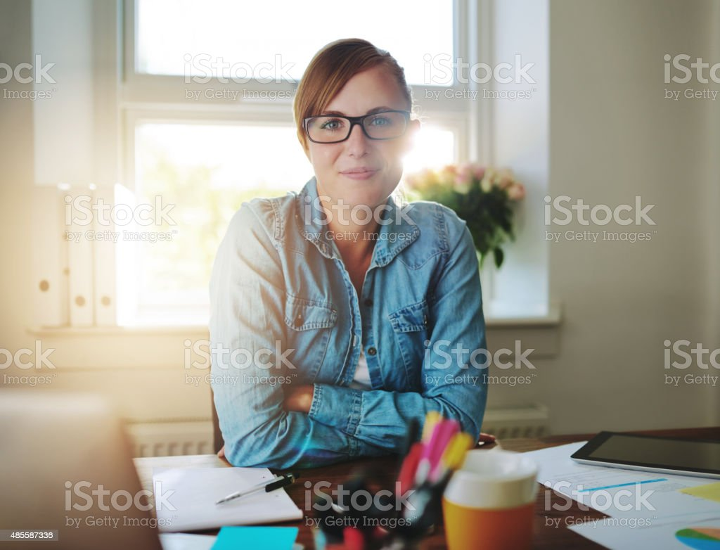 Successful business woman working at the office looking at camera