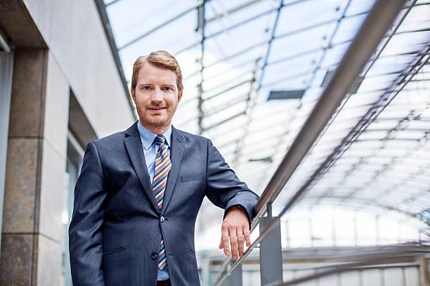 successful businessman at balcony in office - alvarez stock-fotos und bilder