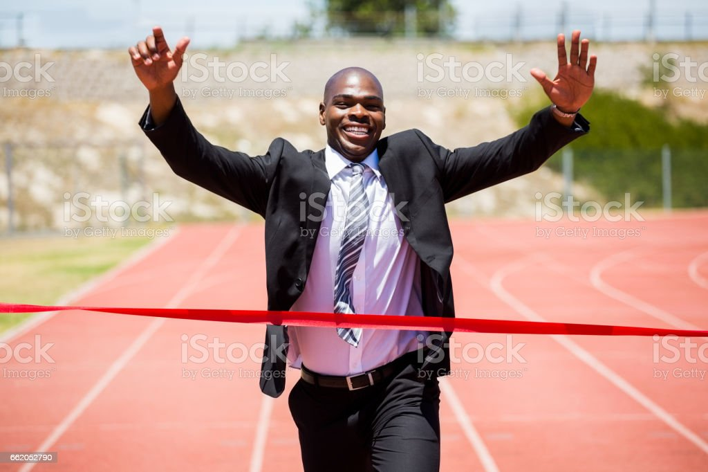 Successful businessman crossing the finishing line royalty-free stock photo