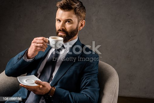 1081599130 istock photo successful businessman drinking coffee and holding saucer 1081599156