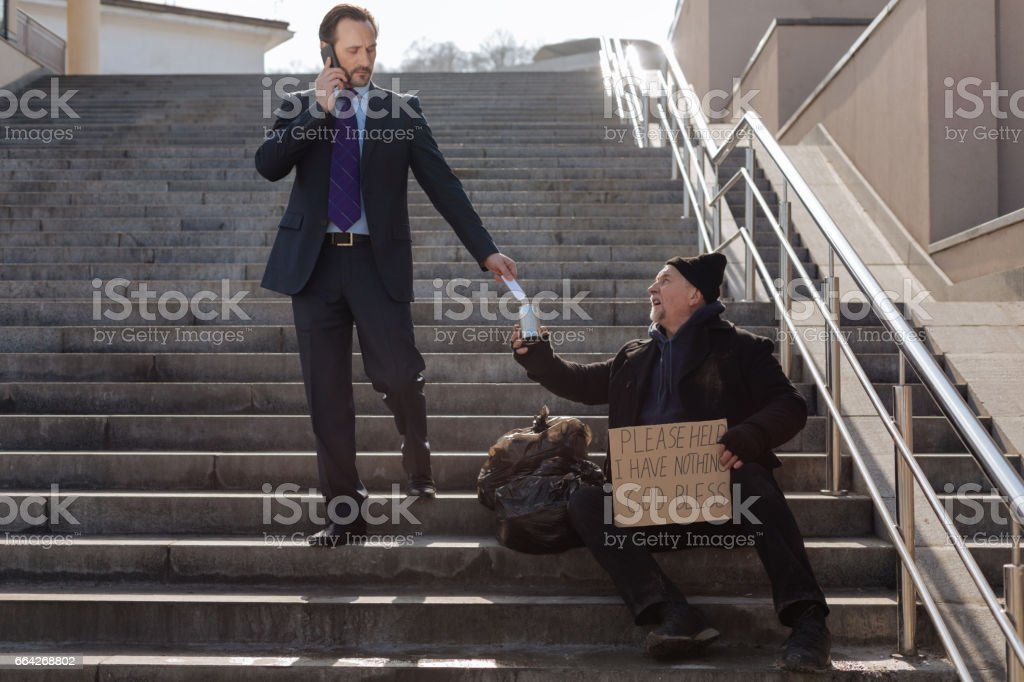 Successful businessman giving money to poor man stock photo