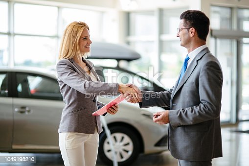 istock Successful businessman in a car dealership - sale of vehicles to customers 1049198210