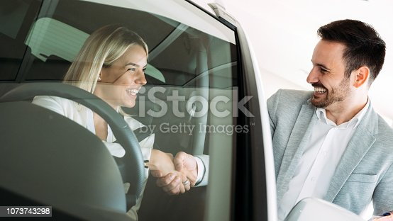 1049198210 istock photo Successful businessman in a car dealership - sale of vehicles to customers 1073743298