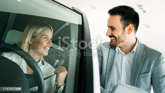 1049198210 istock photo Successful businessman in a car dealership - sale of vehicles to customers 1147512398