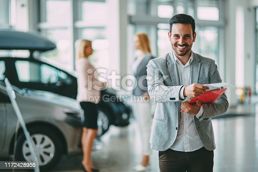 1049198210 istock photo Successful businessman in a car dealership - sale of vehicles to customers 1172428955