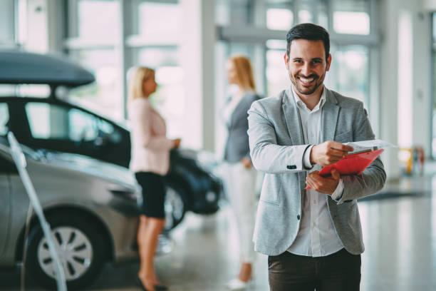 Erfolgreicher Geschäftsmann in einem Autohaus - Verkauf von Fahrzeugen an Kunden – Foto