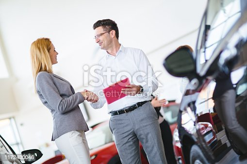 1049198210 istock photo Successful businessman in a car dealership - sale of vehicles to customers 1172430046
