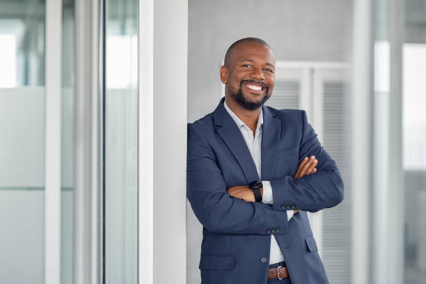 Successful businessman in modern office Mature cheerful african american executive businessman at workspace office. Portrait of smiling ceo at modern office workplace in suit looking at camera. Happy leader standing in front of company building. african american ethnicity stock pictures, royalty-free photos & images