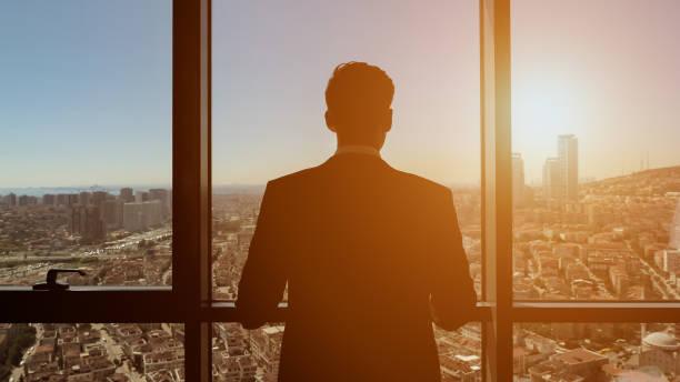erfolgreicher geschäftsmann blickt von seiner modernen wohnung auf den panoramablick auf die stadt. - fensterfront stock-fotos und bilder
