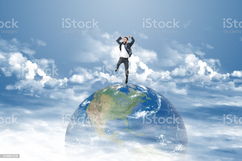 Successful businessman jumping on top of the world stock photo