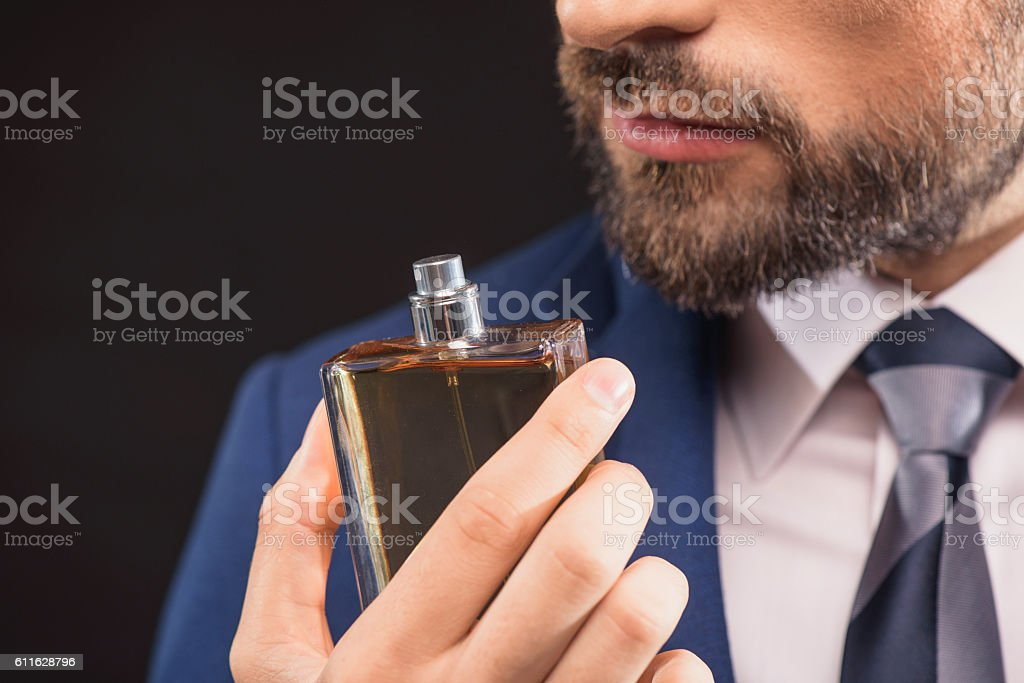 Successful businessman likes perfume scent stock photo