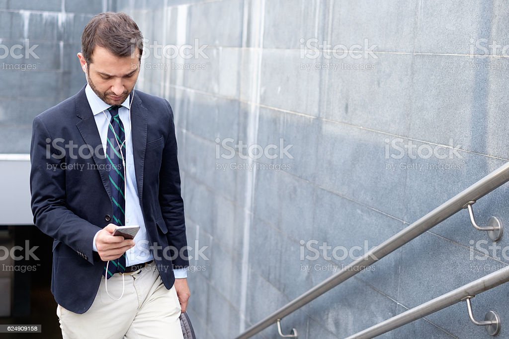Successful businessman looking on his smartphone in the city str - foto stock