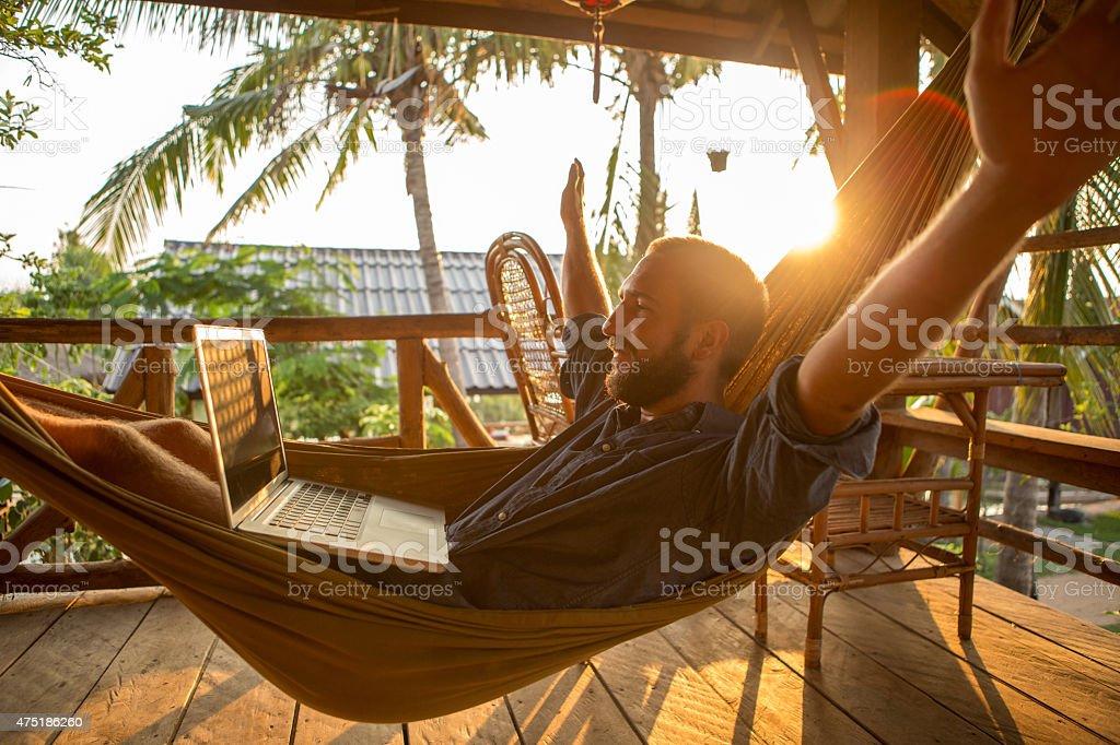 Erfolgreicher Geschäftsmann auf der Hängematte mit computer-Sonnenuntergang – Foto