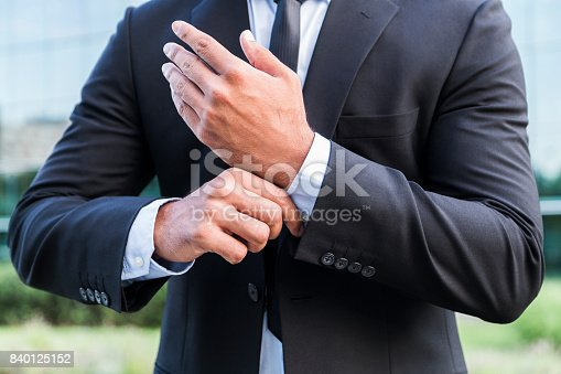 istock Successful businessman or worker standing in suit and straightens shirt 840125152