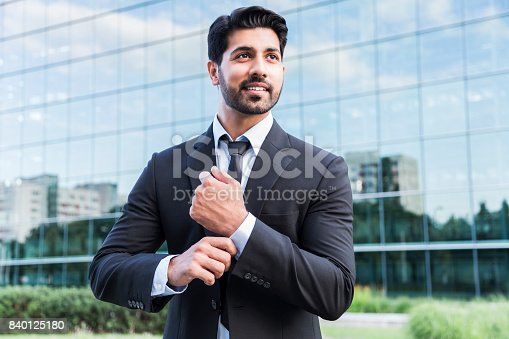 istock Successful businessman or worker standing in suit and straightens shirt 840125180