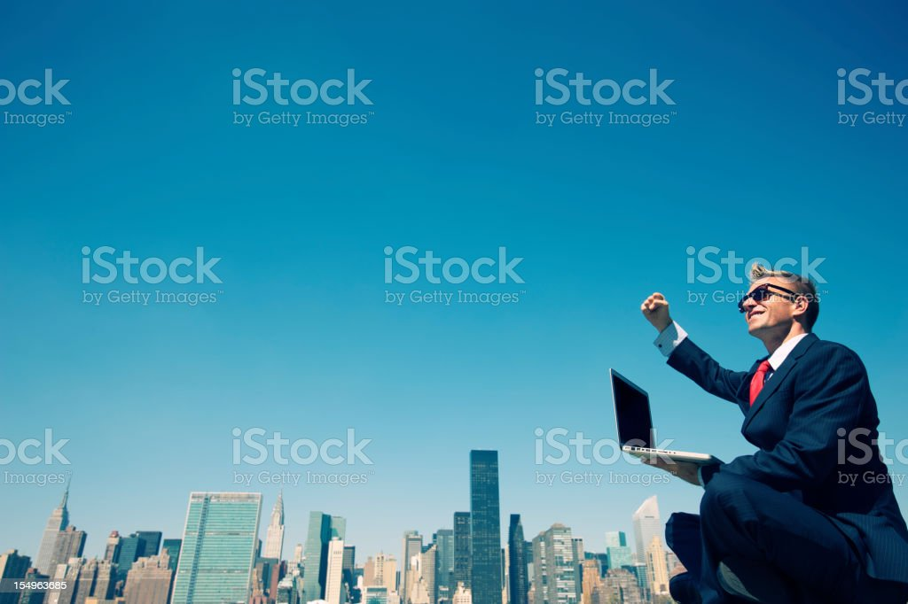 Successful Businessman Pumps Fist Working Outdoors on Laptop City skyline royalty-free stock photo