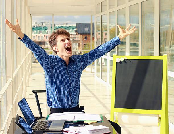 Successful businessman raising arms at workplace. stock photo