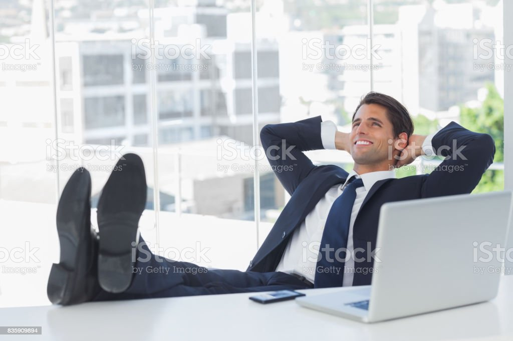 Successful businessman relaxing with his feet on his desk stock photo