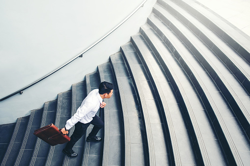 684803840 istock photo Successful businessman running fast upstairs Success concept 1062330914