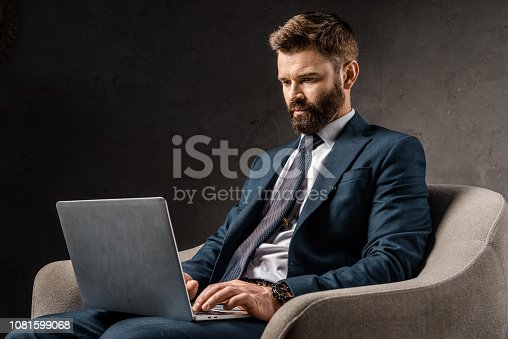 1081599130 istock photo successful businessman sitting in armchair and typing on laptop 1081599068
