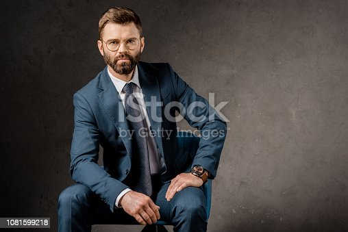 1081599130 istock photo successful businessman sitting in glasses and suit 1081599218