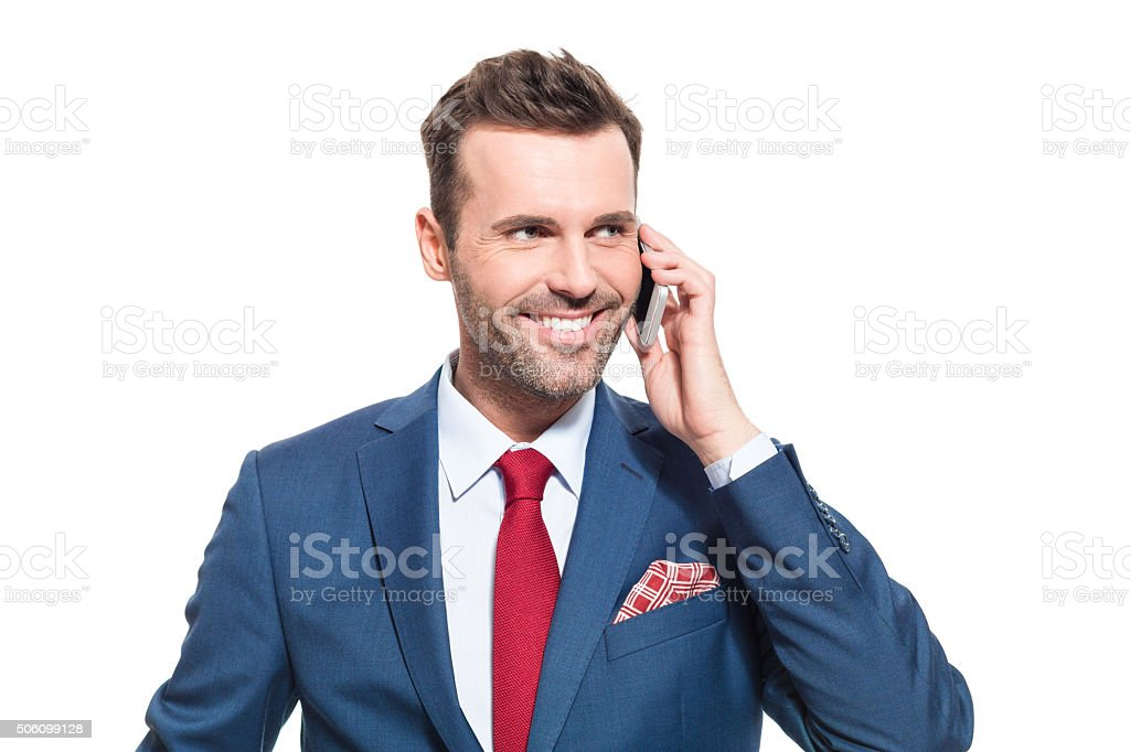 Successful businessman talking on smart phone Portrait of elegant businessman wearing elegant suit, talking on cell phone. Studio shot, one person, isolated on white. Adult Stock Photo