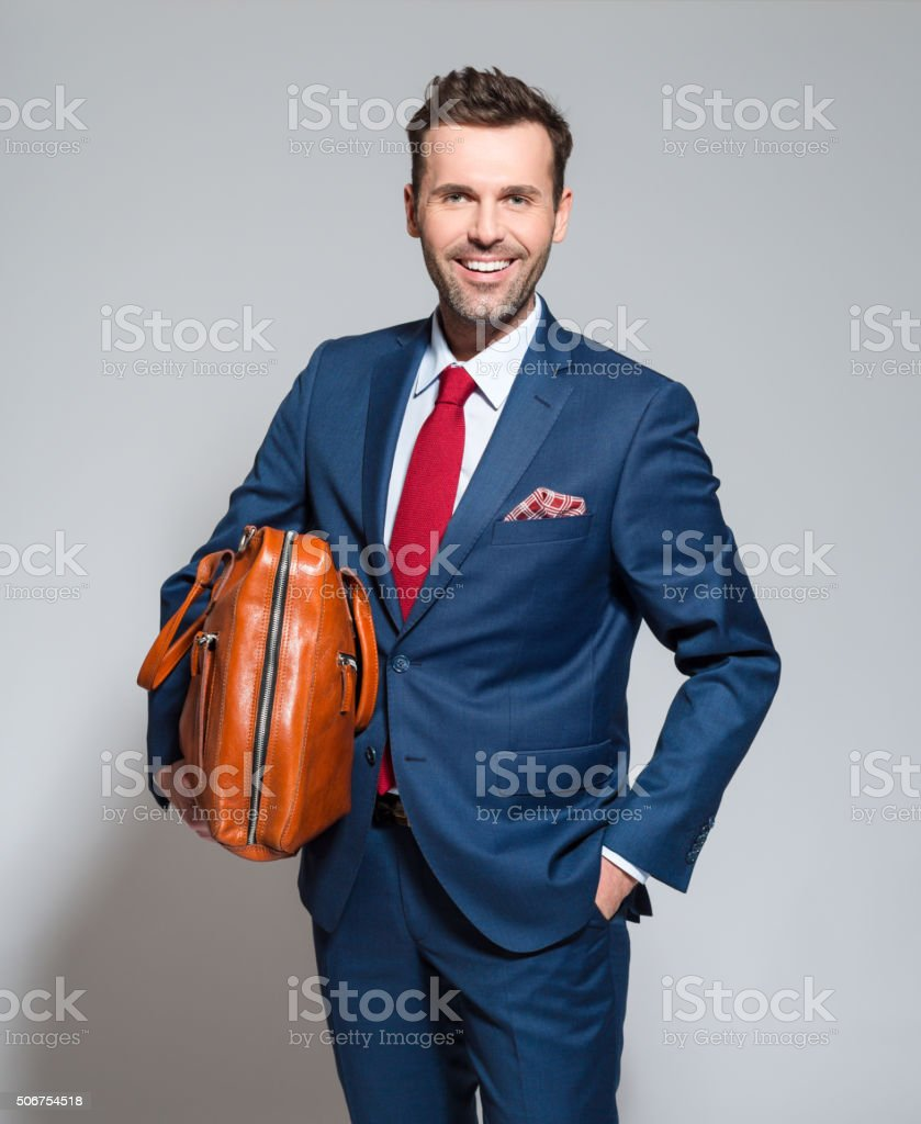 Successful businessman wearing elegant suit, holding briefcase Portrait of elegant businessman wearing elegant suit, holding a leather briefcase, smiling at camera. Studio shot, one person, grey background. Adult Stock Photo