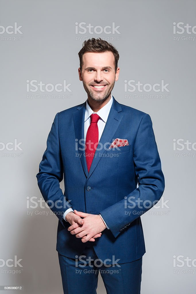 Successful businessman wearing elegant suit Portrait of elegant businessman wearing elegant suit, smiling at camera. Studio shot, one person, grey background. Adult Stock Photo