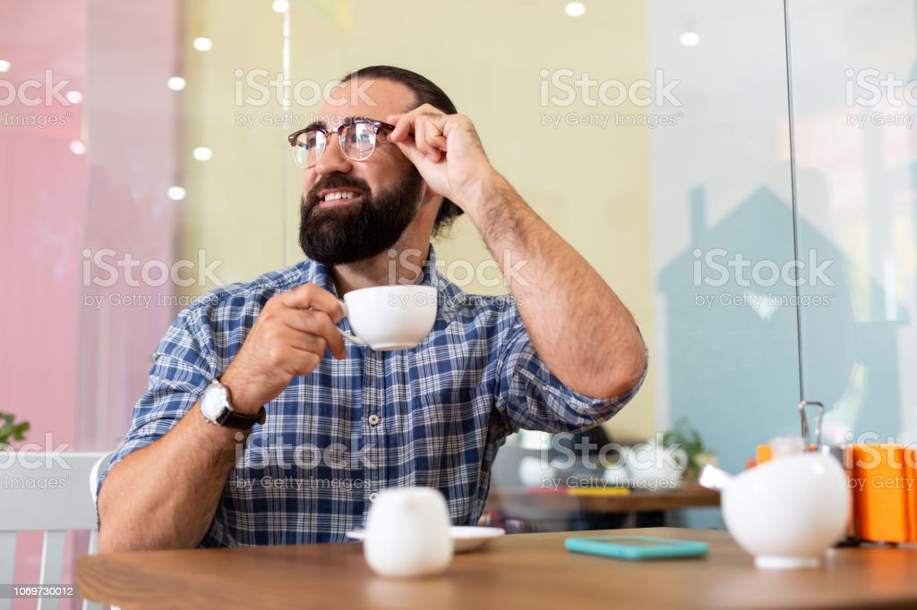 Coffee break. Successful bearded pleasant businessman wearing glasses...