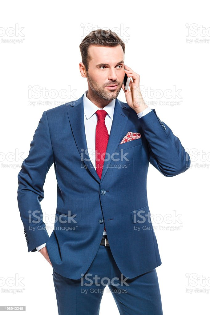 Successful businessman wearing suit talking on cell phone Portrait of elegant businessman wearing suit talking on mobile phone. Studio shot, one person, isolated on white. 2015 Stock Photo